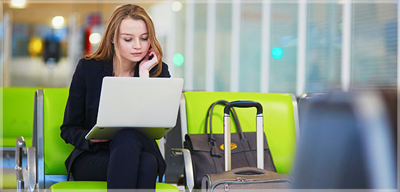 woman in airport working on her laptop
